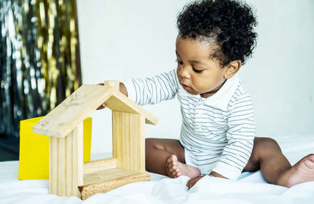 African american cute baby boy playing with wood home toy, He feeling happy.