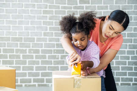 Happy family packing boxes in room. A Little african daughter helps her mum pack boxes in the house. Prepare to move