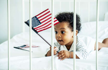 African american cute baby boy holding american flag on bed