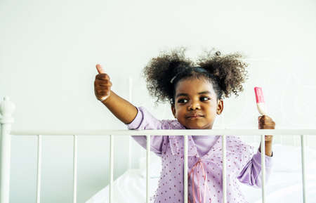 African american cute baby girl  holding eating enjoying delicious  ice cream and thumbs up on bed in bedroom Standard-Bild