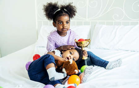 Happy cute active little african american kids boy and girl relaxing on bed at home