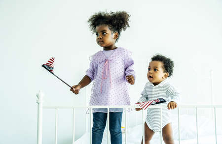 Happy cute active little african american kids boy and girl holding american flag on bed Standard-Bild