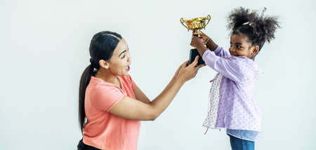 African american daughter express exciting after get reward as trophy from her mother, holding a trophy high up