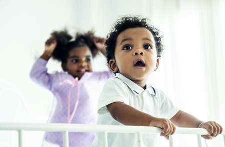 Happy African American naughty kids boy and girl jumping on the bed with happiness.two funny small energetic mixed race children brother with sister having fun play on bed