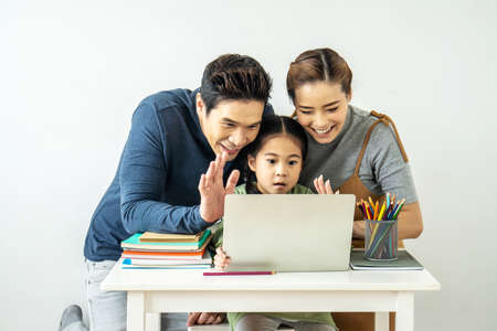 Happy young mother and father and little daughter making video call with laptop computer, gesturing hi, having conversation with  grandfather or grandma using wireless internet connection