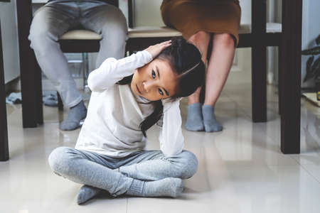 Asian little daughter sad and Clog the ears under table while parent quarrelling in kitchen, Photo design for family problems and unhappy concept