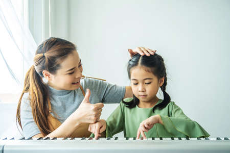 Happy family playing at home, The mother was delighted with the little daughter with a thumbs up to be able to play the piano.