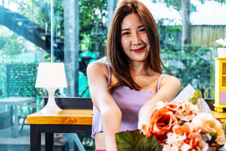 Charming smiling young asian woman standing gives bouquet of flowers indoors in cafe, Giving Spring flowers 免版税图像