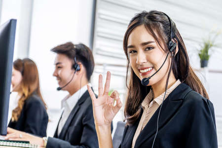 Young asian business woman with headset showing okay hand sign, Call center operator at work