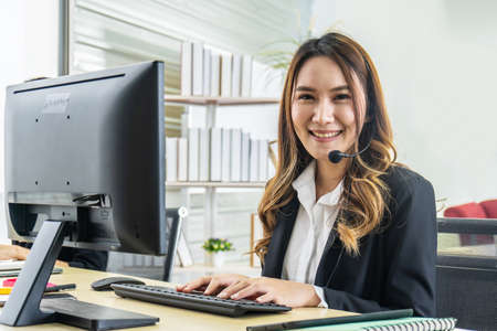 Smiling friendly asian female call-center agent with headset working on support hotline in the office Stock Photo