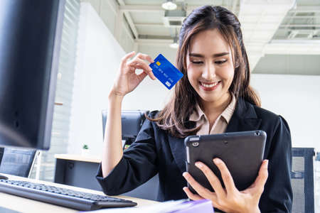 internet banking, online shopping and technology concept, happy smiling asian woman using tablet and credit card to shop online at office