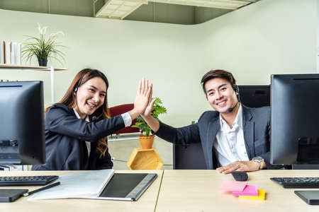 Business men and woman with headset as call center or business telesales on desk at the customer service office giving high five to be pleased with the success