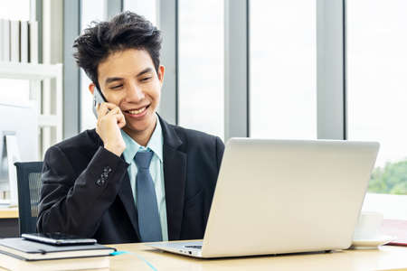 Smiling young asian businessman sitting at desk  talking on mobile phone and using laptop in workplace