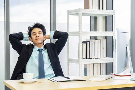 Young asian businessman having break and resting holding hands behind head and keeping eyes closed while sitting at his working place Stock Photo