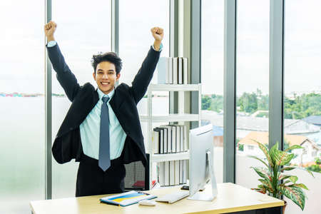 Cheerful BusinessMan Celebrating Success in office, employee got promoted or having great opportunity, applicant received job concept,arms outstretched