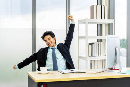 Young asian businessman working at desk in office stretching his arms at workplace