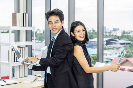Businessman and businesswoman stand back to each other in suits smiling at the camera and working on laptops in office