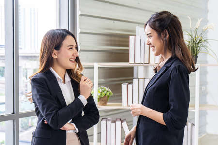 Smiling two business woman talking with partner while standing in modern office interior, team of professional employees discussing ideas of project after meeting