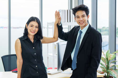 Well done! Smiling asian female and male company colleagues giving high five in office, excited with starting partnership Stock Photo