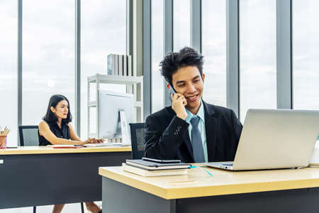 Young businessman sitting at office talking on mobile phone, sitting at desk, using laptop, smiling, businesswoman working on laptop in her workstation in background. Stock Photo