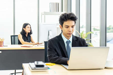 Young asian businessman sitting at desk working on laptop and businesswoman working on laptop in her workstation in background. Stock Photo