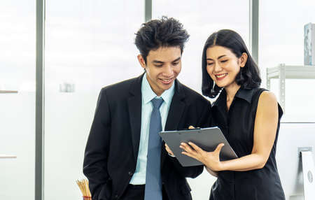 Professional asian business woman holding document file on hand and talk about business plan with business man in the workplace.
