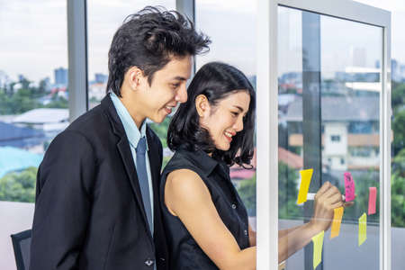 Asian creative business women and man are writing note on the text sheet after thinking new idea and planning project with colleague ,Group of employee brainstorming idea on glass wall and sticky