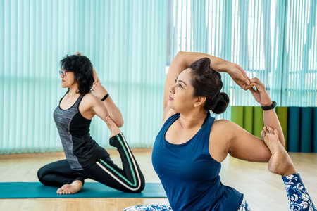 Fit woman practice yoga with friends, Young, woman in yoga class making beautiful asana exercises. Girl do mermaid pose, variation of rajakapotasana. Healthy lifestyle in fitness club.
