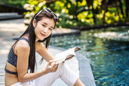 Beautiful young asian woman sits on the pool's edge outdoors. She reading book while relaxing near swimming pool