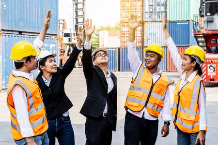 Group of employees and management team wearing logistic uniforms for exporting products abroad, stand to put your hands up and raise your hands together for a harmonious work experience 版權商用圖片