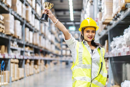 Happy woman warehouse worker holding a trophy after being selected as an outstanding employee Archivio Fotografico