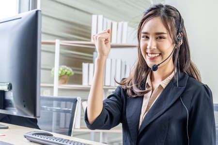 Smiling beautiful businesswoman with headset working in call center as a customer service agent celebrating a good job in the workplace