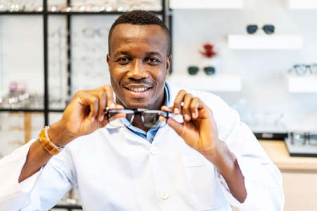 Ophthalmologist doctor african american man showing eyeglasses with new lenses for vision into the camera, Optician giving new glasses to customer for testing and trying
