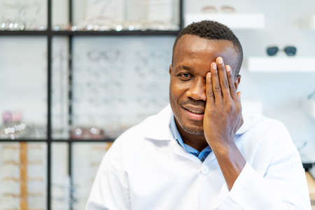 Eyesight And Vision Concept. View of smiling african american attractive optician covering one eye with palm as if having his eyes tested during vision examination Standard-Bild