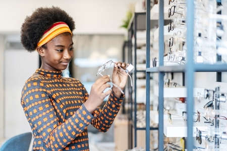 Need a new glasses. Young woman african american in optic store choosing a new eyeglasses frame. Medical, health care concept, used correct or assist defective eyesight