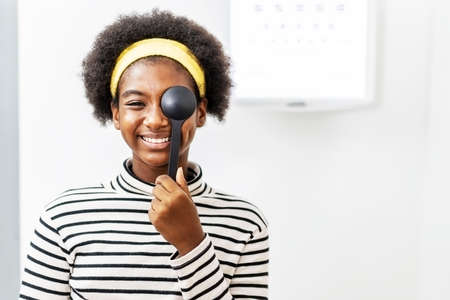 Smiling young woman african american doing eye test in ophthalmological clinics, holding occluder and looking at chart, Eyesight correction, Optics clinic