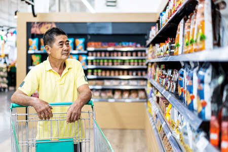 Asian senior man shopping trolley choosing other products in supermarket Standard-Bild