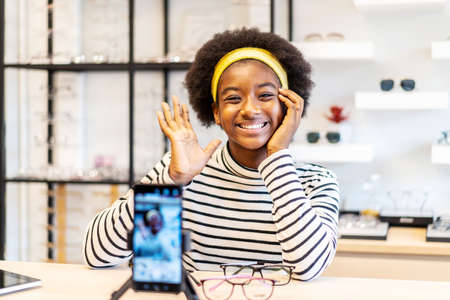 Young woman african american entrepreneur is fashion vlogger show glasses to cellphone and smiling selling it online live streaming in eyeglasses shop