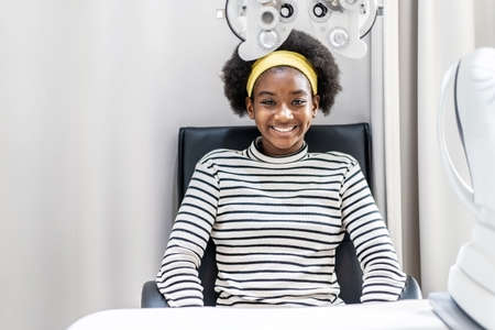 Smiling young woman african american afro hair after doing eyesight measurement with optical phoropter