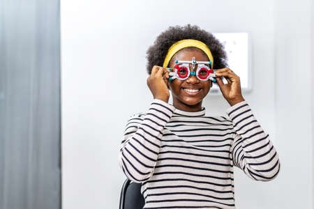 Smiling young woman african american checking vision with eye test glasses during a medical examination at the ophthalmological office, Checking eye vision by optician health examination concept