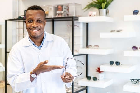 Eyesight And Vision Concept. Portrait of smiling african american standing at optics store and pointing at showcase and rack with many eyewear and specs frames. Guy offering spectacles Standard-Bild