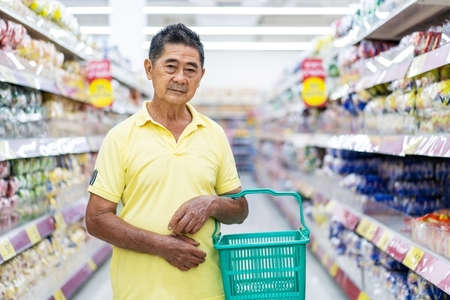 Asian senior man shopping in a supermarket, Elderly customer with a shopping basket in a supermarket