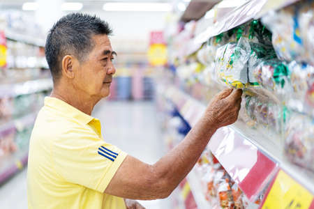 Portrait of man customer choosing and buying food at the supermarket