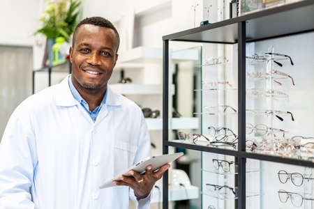 Eyesight And Vision Concept. View of smiling african american attractive optician working with tablet in his glasses shop.