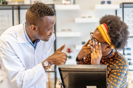 African american man professional optician helping and selling young woman african american choosing spectacles glasses in optician store. used correct assist or defective eyesight.