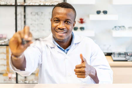 Ophthalmologist doctor african american man showing eyeglasses with thumbs up for vision into the camera, Optician giving new glasses to customer for testing and trying Standard-Bild