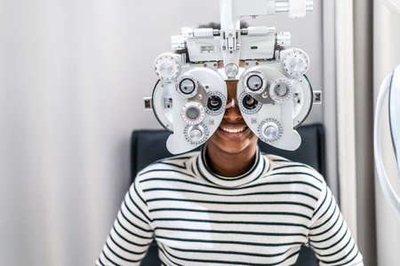 Smiling young woman african american afro hair doing Eye test on optical phoropter, checking on her eye with optometry machine