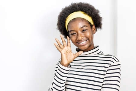 Cute african american girl wearing casual clothes waving saying hello happy and smiling, friendly welcome gesture