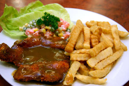 De-boned chicken chop with rich mushroom sauce, fries, coleslaw, leaf of lettuce and parsley Stock Photo - 291228
