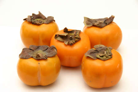persimmons: Five persimmons arranged as on dice, on a white surface and background